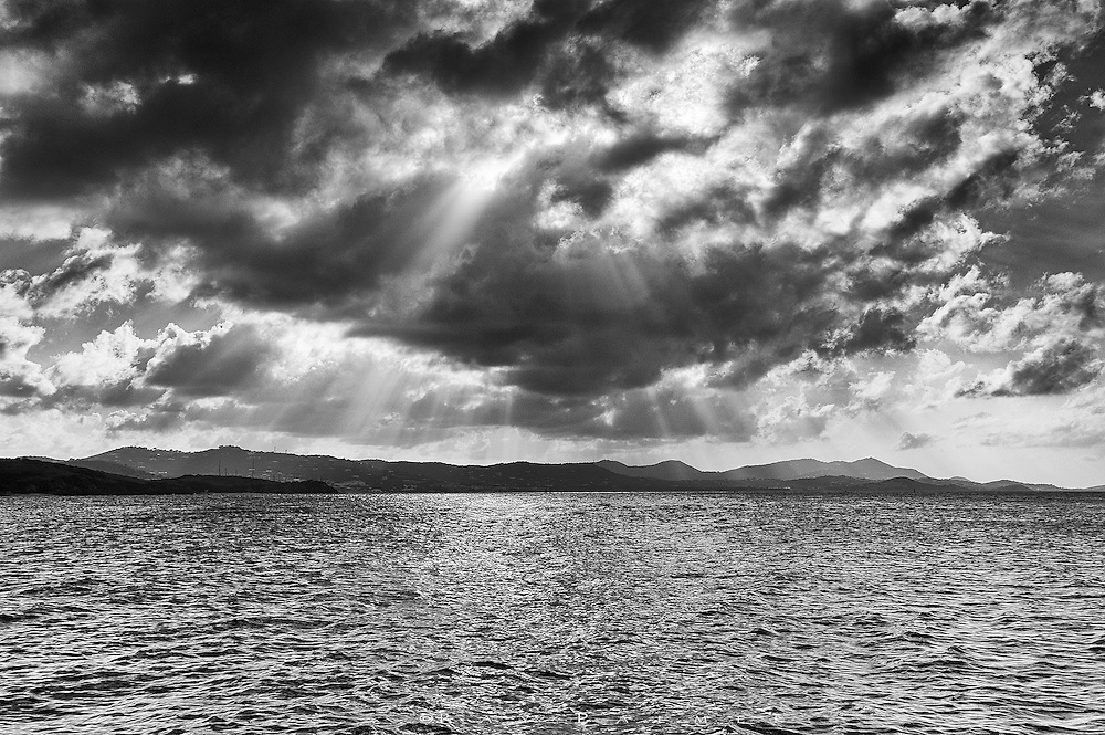 St Croix, USVI_RP1630210<br /> Sailing out of Christiansted, late in the afternoon, the wind lulled and the sky darkened.  As we rocked and the captain watched the sails, big beams of light shot through the clouds and highlighted  the mountains.  There was no swell, just a fine chop on the water that pattered against the hull, a sound enhanced because no one spoke, transfixed by the scene.  Crepuscular rays--God rays--are an atmospheric phenomenon of parallel shadows from the dark clouds and light as it pertains to your earthbound, physical perspective.  But I think the scientific explanation faded in the quiet, with eyes following the sunbeams up like escalators, beyond the black and into the blue...