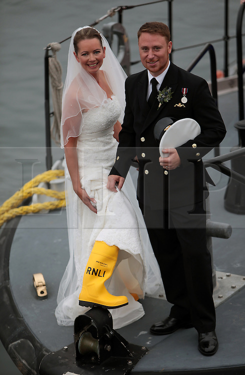 Licensed to London News Pictures. 20/07/2013. North Shields, UK, Tynemouth RNLI lifeboat volunteer crewmember Jill McCormick has her marriage to Simon Lee blessed onboard the Tynemouth RNLI lifeboat 'Spirit of Northumberland'. The couple were married an hour earlier at the local registry office before being blessed at the lifeboat station by station Chaplain Rev. Timothy Duff. Jill,35, has been an RNLI volunteer for 12 years and works as a fisheries officer at the Environment Agency. Simon,31, is a Royal Navy submariner and having graduated with an engineering degree is about to begin officer training at Dartmouth College. For more information please contact Adrian Don (RNLI volunteer Press Officer) on 07834 731833. Photo credit: Adrian Don/LNP