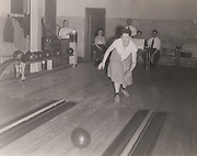 Woman bowling while men in the background look on 1940s