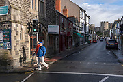 With the medieval castle dominating the town, a couple cross Conwy high street, on 4th October 2021, in Conwy, Gwynedd, Wales. The walls were constructed between 1283 and 1287 after the foundation of Conwy by Edward I, and were designed to form an integrated system of defence alongside Conwy Castle. The walls are 1.3 km (0.81 mi) long and include 21 towers and three gatehouses. Conwy is a walled market town and community on the north coast of Wales.