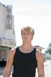 All American man without a shirt outdoors with a blanket All American blond man in a tank top outdoors