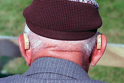 Elderly man wearing hearing aid in both ears UK