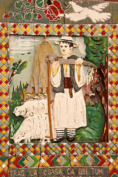 Tombstone showing an shepherd with his sythe,  The  Merry Cemetery ( Cimitirul Vesel ),  Săpânţa, Maramares, Northern Transylvania, Romania.  The naive folk art style of the tombstones created by woodcarver  Stan Ioan Pătraş (1909 - 1977) who created in his lifetime over 700 colourfully painted wooden tombstones with small relief portrait carvings of the deceased or with scenes depicting them at work or play or surprisingly showing the violent accident that killed them. Each tombstone has an inscription about the person, sometimes a light hearted  limerick in Romanian. .<br /> <br /> Visit our ROMANIA HISTORIC PLACXES PHOTO COLLECTIONS for more photos to download or buy as wall art prints https://funkystock.photoshelter.com/gallery-collection/Pictures-Images-of-Romania-Photos-of-Romanian-Historic-Landmark-Sites/C00001TITiQwAdS8