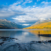 woman stading on lake shore in glacier, national park durning the fall