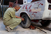 Cuban man of mixed race fixing a wheel onto a car without paint on it, in a garage in Havana old town.