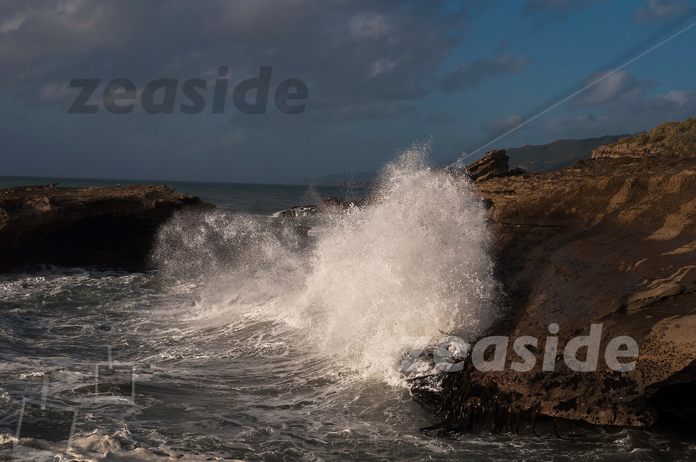 A wave crashing into the limestone formations of the West Coast near Punakaiki in New Zealand.