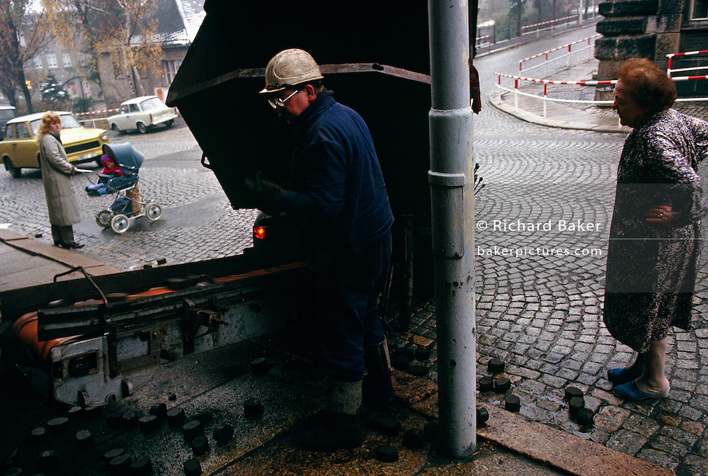 A coal delivery man deposits chunks of brown coal into the cellar via a conveyor belt for an elderly lady who stands outside in the bitter cold wearing only a housecoat this grim day. Her slippers can be seen standing among fallen briquettes that have dropped on to the wet cobbled street as the man oversees the delivery from a truck that has backed on to the pavement near a junction. A passing Trabant car rattles up the hill past a mother who pauses to ensure a safe crossing for her baby. Aue is a mining town in the Ore Mountains known for its copper, titanium, and kaolinite. The town was a machine-building and cutlery manufacturing centre in the East German era with a population of roughly 18,000 inhabitants. It was the administrative seat of the former district of Aue-Schwarzenberg in Saxony and part of the Erzgebirgskreis since August 2008..