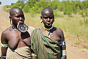 two women of the Mursi tribe with clay lip disc as body ornamentstribe Debub Omo Zone, Ethiopia. Close to the Sudanese border.