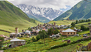 Stone medieval Svaneti tower houses of Chvibiani with mount Shkhara (5193m) behind, Ushguli, Upper Svaneti, Samegrelo-Zemo Svaneti, Mestia, Georgia.  Chvibiani is a group of four remote villages. At 2,200 m (7217 ft) above sea level in the Caucasus mountains these are the highest inhabited villages in Europe. Chvibiani has well preserved stone Svanetian defensive tower houses attached to stone family houses. Mount Shkhara is the highest mountain in the Caucasus range.  A UNESCO World Heritage Site. .<br /> <br /> Visit our REPUBLIC of GEORGIA HISTORIC PLACES PHOTO COLLECTIONS for more photos to browse, download or buy as wall art prints https://funkystock.photoshelter.com/gallery-collection/Pictures-Images-of-Georgia-Country-Historic-Landmark-Places-Museum-Antiquities/C0000c1oD9eVkh9c