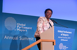 © Licensed to London News Pictures. 22/10/2018. Bristol, UK. Global Parliament of Mayors Annual Summit, 21-23 October 2018, at Bristol City Hall. Picture of CHRISTINE MUSISI, Director of External Relations, UN-Habitat, addressing the conference. The Global Parliament of Mayors 2018 is the biggest and most ambitious Annual Summit to date. GPM Bristol 2018 will host up to 100 global mayors for an action-focused summit that addresses some of the biggest challenges facing today's world cities. GPM Bristol 2018's theme, Empowering Cities as Drivers of Change, will focus minds on global governance and the urgent need for the influence, expertise and leadership of cities to be felt as international policy is shaped. GPM Bristol 2018 will provide mayoral delegates with a global network of connections and a space to develop the collective city voice necessary to drive positive change. The programme will engage participants in decision-making, with panels, debate and voting on priority issues including migration and inclusion, urban security and health, and is a unique chance to influence decisions on the most pressing issues of our time. Photo credit: Simon Chapman/LNP