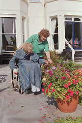 Carer with elderly woman in wheelchair looking at flowers outside residential home,