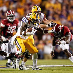 November 3, 2012; Baton Rouge, LA, USA; LSU Tigers running back Jeremy Hill (33) breaks away from Alabama Crimson Tide defensive back Nick Perry (27) and linebacker Xzavier Dickson (47) during the first quarter of a game at Tiger Stadium.  Mandatory Credit: Derick E. Hingle-US PRESSWIRE