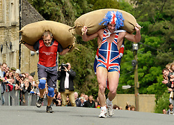 © Licensed to London News Pictures. 04/06/2012. Tetbury, Gloucestershire, UK. Joel Hicks (in Union Jack) from Leicester travelled to Tetbury to compete in the annual Woolsack race racing with sacks of wool up a steep hill in the town. Joel tripped  and fell during the race. The Royal Jubilee celebrations. Great Britain is celebrating the 60th  anniversary of the countries Monarch HRH Queen Elizabeth II accession to the throne this weekend Photo credit : Simon Chapman/LNP
