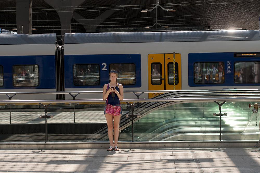 Op station Rotterdam Centraal wacht een meisje op de trein terwijl ze bezig is met haar telefoon. Wegens verwachte warmte zet NS op sommige trajecten minder treinen in.<br /> <br /> At Rotterdam Central Station a girl is busy with her phone while waiting for the train.