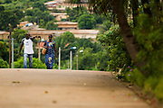 HIV/AIDS counselor Kevin Kouassi Gallet and coworker Joelle Kouakou Oussou walk along a road to go visit the Djaha family in Dimbokro, Cote d'Ivoire on Friday June 19, 2009.