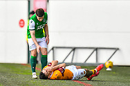 Tony Watt (#32) of Motherwell FC goes down holding his face after an accidental clash with Lewis Stevenson (#16) of Hibernian FC during the SPFL Premiership match between Hibernian FC and Motherwell FC at Easter Road, Edinburgh, Scotland on 27 February 2021.