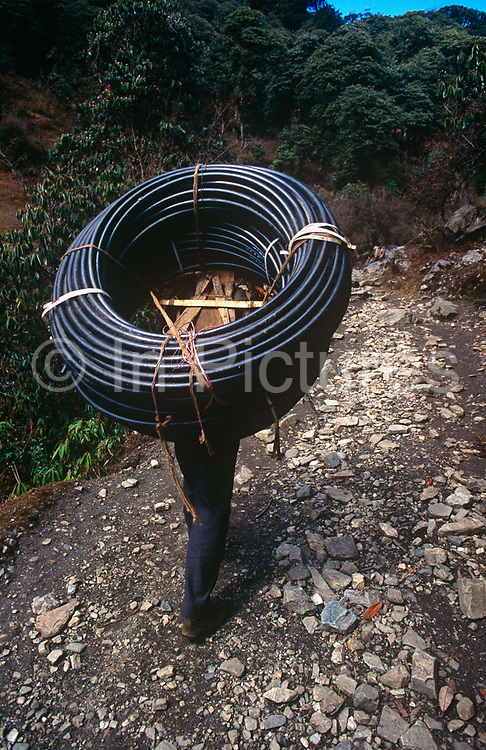 A local man carries electric cabling uphill on the Annapurna Sanctuary trekking route in central Nepal. With few roads that can transport supplies and raw materials up to remote foothill communities, the only way is often to carry what one needs on the back or by yak. The paths are even but often very steep in places so stamina and endurance are needed to get even modest weights uphill. Nepalis up here often want newer technology and basic electricity to power lights and showers although solar power is another answer.