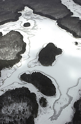 Lake Hammonasset from the air. Aerial View in Winter of the iced over Lake and Snow covered woodlands surrounding.