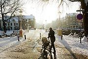 Een vrouw loopt met een kinderwagen door een besneeuwd Utrecht.<br /> <br /> A woman is walking with a stroller in a snowy Utrecht.