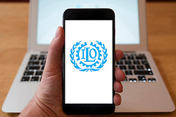 Using iPhone smartphone to display logo of ILO, International Labour Organization. UN agency to set labour standards.