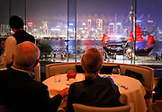 A couple enjoying a night view of Hong Kong and passerby boats from a hotel bar in Kowloon.
