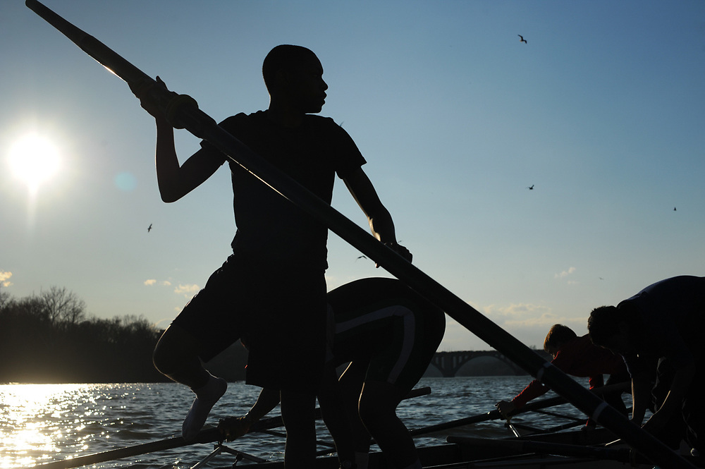 Crew members of the Woodrow Wilson High School Novice rowing team dock their boat at the end of practice at the Thompson Boat Center in Northwest Washington.