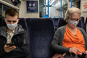 Rail passengers on a train service through south London wear facial coverings and sit socially distant during the Coronavirus pandemic, on 24th August 2020, in London, England.