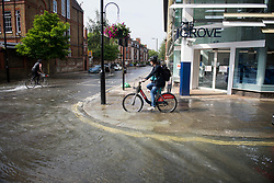 © Licensed to London News Pictures. 24/06/2021. London, UK. Two cyclists make their way through a river of water in St John's Wood, North London, where a burst pipe has has cause flooding across a number of streets in the area. Photo credit: Ben Cawthra/LNP