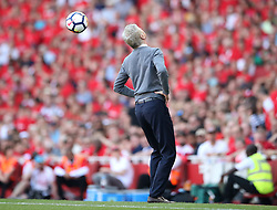 Arsenal manager Arsene Wenger heads the ball back into play from the touchline during the Premier League match at the Emirates Stadium, London.