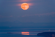 Telephoto view of full moon over the  the Dungeness Spit  and Salish Sea, North Olympic Peninsula, Washington, USA