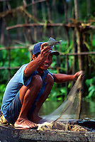 Vietnamese fishermen in the Mekong Delta, near Saigon, laughs as he shows off his catch.