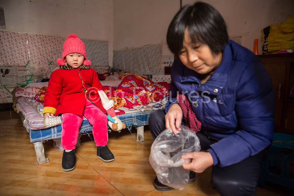 Zhao Jing and her grandmother Li Defang, on a bed in their apartment in the Wujianong neighborhood of Hefei, China, on Thursday, Nov. 26, 2015. Cheap housing in the neighbourhood and its closeness to the regional children hospital has made it a popular long term stay option for many families with kids suffering from caner, notably Leukaemia, as Surging health-care costs are turning into one of the biggest threats to the world's second largest economy and its consumers.