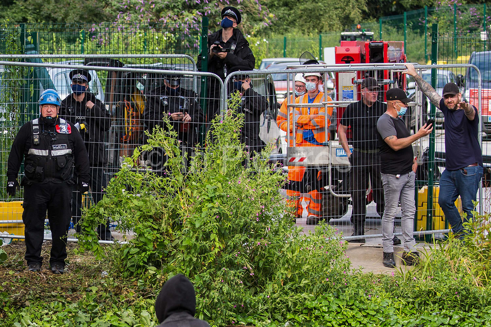 Enforcement agents, police officers and HS2 workers observe environmental activists from HS2 Rebellion who were attempting to protect an ancient alder tree from destruction in connection with works for the HS2 high-speed rail link on 24th July 2020 in Denham, United Kingdom. A large security operation involving officers from the Metropolitan Police, Thames Valley Police, City of London Police and Hampshire Police as well as the National Eviction Team ensured the removal of the tree by HS2 despite the protests by activists.