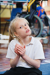 Girl with physical and learning difficulties clapping her hands,