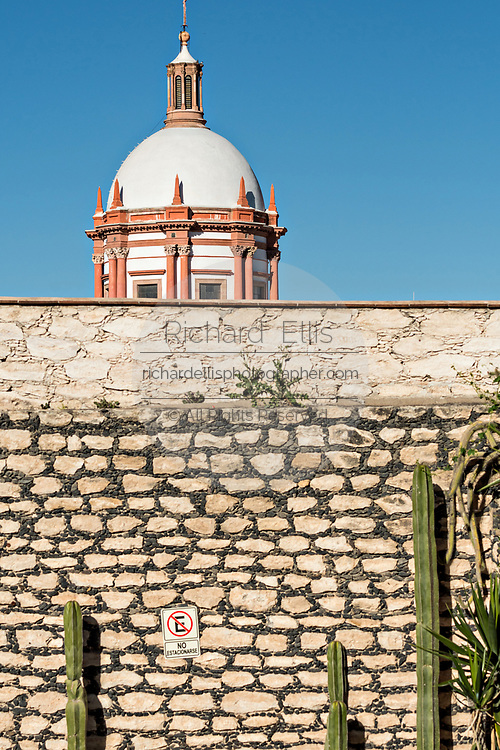 The dome of the Parroquia de San Pedro Apóstol church or Saint Paul the Apostle provincial church peaks above a stone wall in Mineral de Pozos, Guanajuato, Mexico. The town, once a major silver mining center was abandoned and left to ruin but has slowly comeback to life as a bohemian arts community.