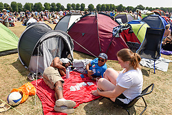 © Licensed to London News Pictures. 06/07/2018. LONDON, UK. Spectators play cards in the sunshine whilst queuing for day tickets in Wimbledon Park to the Wimbledon Tennis Championships.  Temperatures forecast to approach 30C mean that the majority have taken precautions to protect themselves from the sun by wearing sunglasses and sunhats.  Photo credit: Stephen Chung/LNP