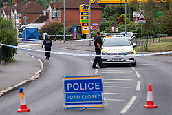 © Licensed to London News Pictures. 31/07/2021. High Wycombe, UK. A police vehicle forms a cordon as a police officer walks towards a forensic tent outside a Jet petrol station as a major police investigation gets underway in High Wycombe, unconfirmed reports on social media indicate that a person was stabbed to death in the early hours of Sunday morning 31 July 2021. Photo credit: Peter Manning/LNP