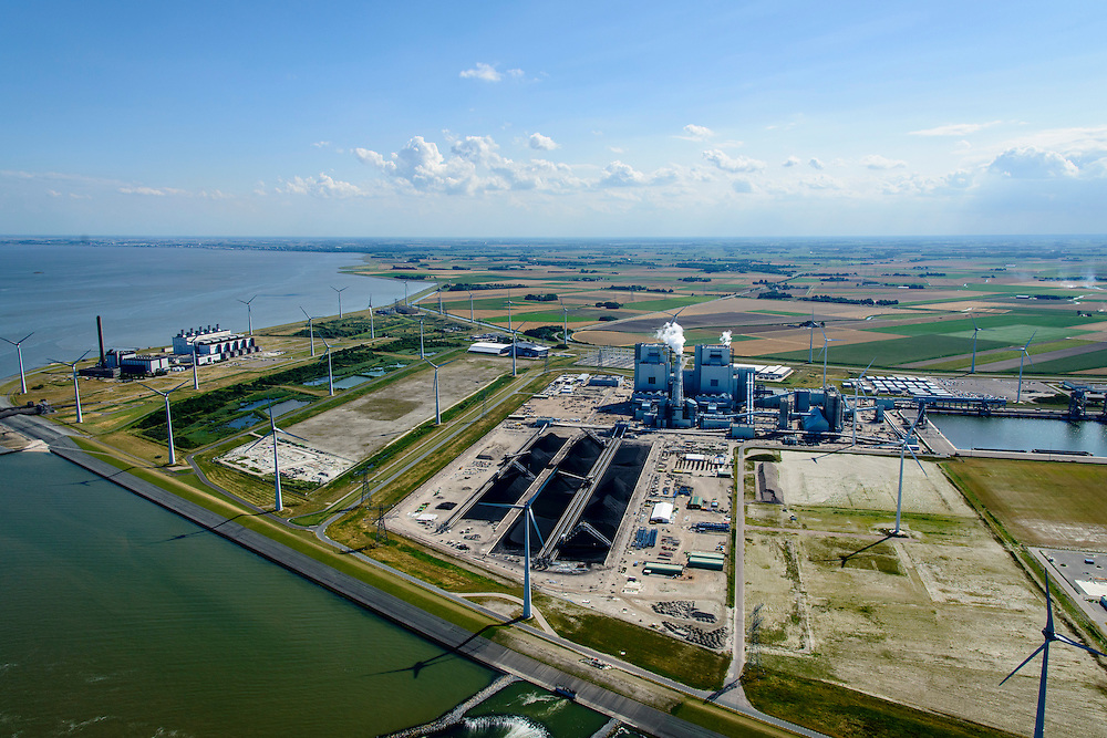 Nederland, Groningen, Eemshaven, 05-08-2014; Haven omzoomd door windmolens. Energie-landschap met elektricitieitscentrales vlinsk de Eemscentrale van Electrabel (stoom- en gascentrale, STEG-centrale - achtergrond). In het midden de RWE-Essent elektriciteitscentrale ( kolencentrale) .<br /> <br /> Harbor area and energy landscape with wind turbines and different power plants: the coal fired  RWE-Essent plant (middle) and the Electrabel STEG  power plant (left).<br /> <br /> luchtfoto (toeslag op standard tarieven);<br /> aerial photo (additional fee required);<br /> copyright foto/photo Siebe Swart