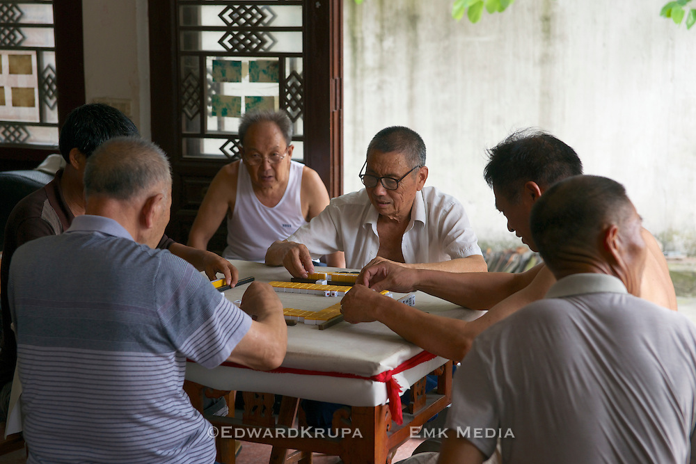 Men playing the popularize Chinese game Mahjong in a temple in China.