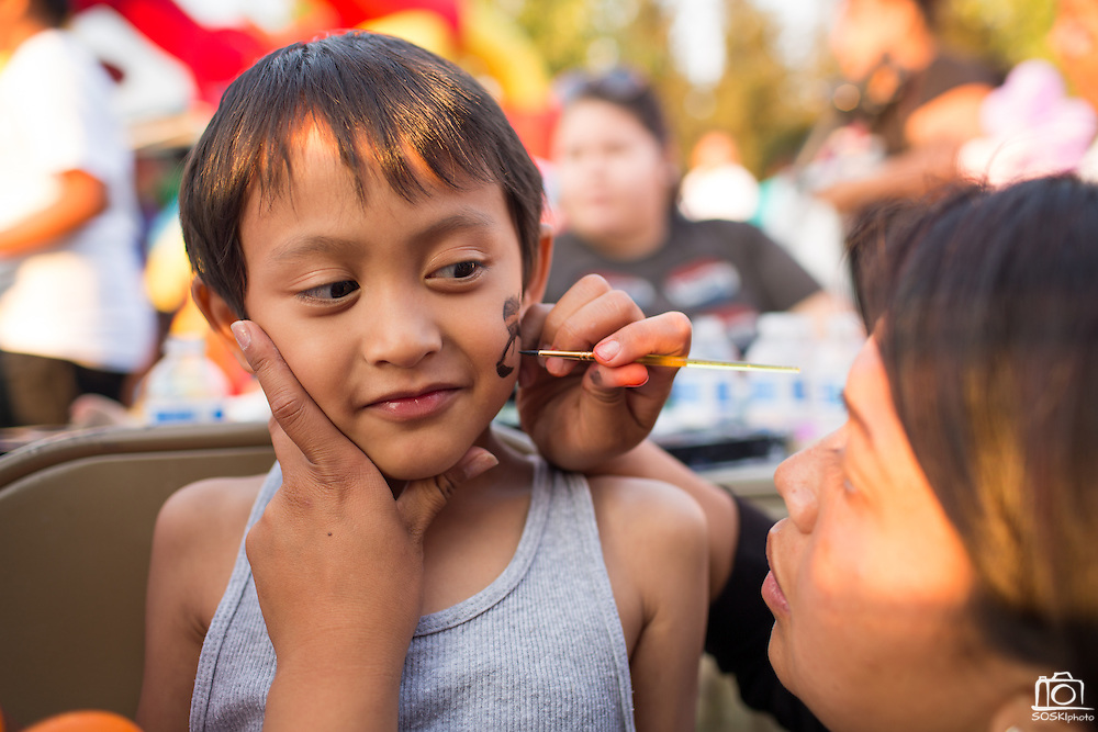 John Erick Ramirez, 5, has a ninja painted on his face during the National Night Out event hosted by Cathedral of Faith Milpitas at Selwyn Park in Milpitas, California, on August 7, 2014. (Stan Olszewski/SOSKIphoto)