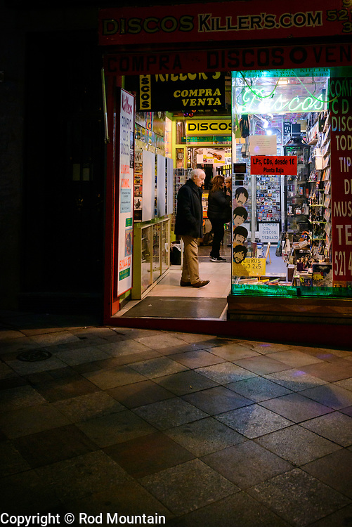 Madrid, Spain - February 15, 2018 - A little late night shopping at a local record & cd store.<br /> <br /> Image: © Rod Mountain http://www.rodmountain.com http://bit.ly/RM-archive<br /> <br /> Nikon D800 / Nikkor Lens #NikonCA #NikonNoFilter #NikonEurope<br /> <br /> @spain @visita_madrid @NikonUSA @nikoncanada @nikoneurope<br /> <br /> @spain.info @visitamadridoficial @NikonUSA @nikoncanada @nikoneurope @DISCOS-KILLERS-126931594054322<br /> <br /> @spain @Visita_Madrid @NikonUSA @nikoncanada @nikoneurope @TurismoMadrid<br /> <br /> https://en.wikipedia.org/wiki/Madrid https://www.spain.info/en/ http://discoskillers.com/shop/<br /> <br /> #Spain #TourismSpain #VisitSpain #VisitMadrid #timeless_streets #streetphotographyworldwide #streetsgrammer <br /> #capturestreets #life_is_street #nightwalkermagazine #IamATraveler #exploretocreate #journey #ontheroad #monochrome #blackandwhiteonly #bnw_street #streetscene #stayandwander #Hotel #Night #NightPhotography #NightShooterz #travelersnotebook #walkabout #Madrid #bw