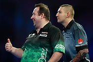 Brendan Dolan puts his thumb up to the referee and Nathan Aspinall looks on, as they ask for the board to be straightened before the mtach, during the World Darts Championships 2018 at Alexandra Palace, London, United Kingdom on 29 December 2018.