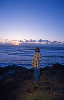 A man watches the sunset over The Pacific Coast from Sea Ranch, California.
