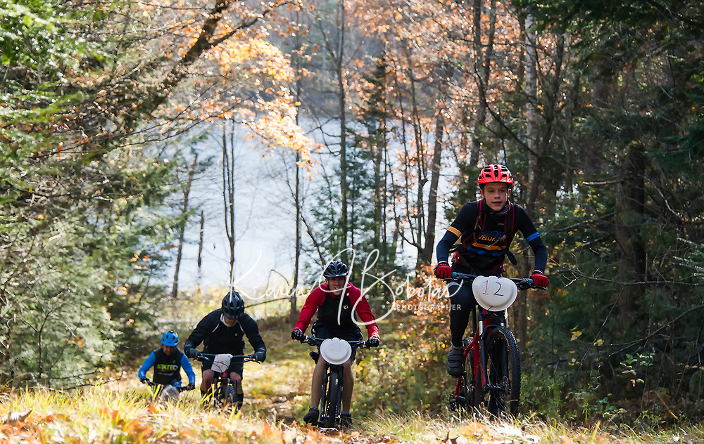 Lance Cote, Aaron Costello, Stephen Burns and Alex Indeck grind up Rock Loop trail during the Fall Flurry mountain bike race at Gunstock Saturday morning.  (Karen Bobotas/for the Laconia Daily Sun)