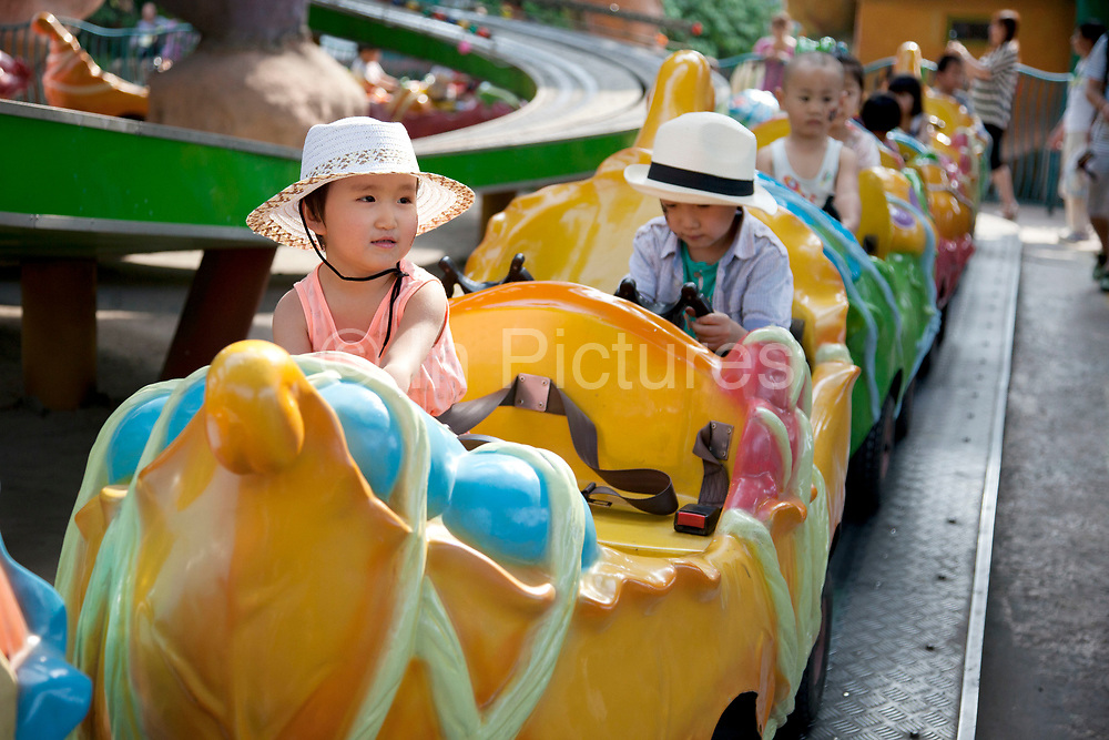 Young children enjoying a gentle ride. Happy Valley Beijing is an amusement park in Beijing, China built and operated by Beijing OTC, which is part of the Shenzhen OCT Holding Group. The park, which is located in the east of Beijing, opened in July, 2006. It is one of four theme parks in the brand chain. Similar in style with the Disney land park, Happy Valley Beijing also featured distinctive landscapes and themes throughout the resort along with featured rides within the different themes. In total there are more than 40 rides.