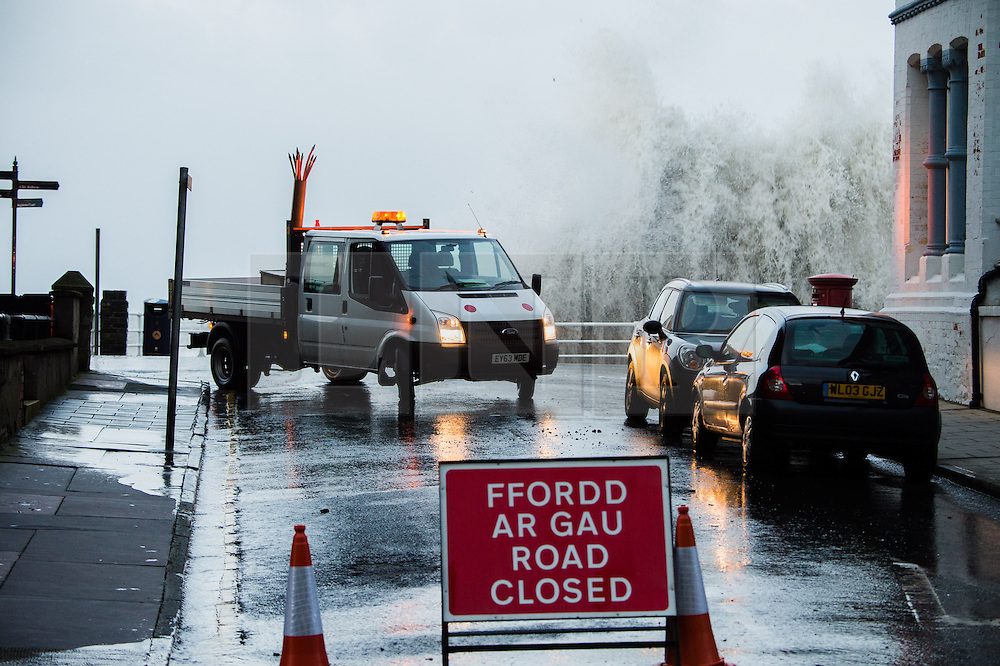 © London News Pictures. Aberystwyth, Wales. 03/01/2014. A road closed on the seafront. A 5.6m high springtide and gale force south westerly winds bring  massive weaves pounding against the promenade and harbour at Aberystwyth on the west wales  coast.  The entire promenade was  closed to traffic because of fears for safety. Over 20 severe warnings have been issued for flooding in England and Wales, with the weather set to worsen over the next 24 hours, Across much off the south and west coast. Photo credit: Keith Morris/LNP