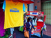 "03 JULY 2018 - BANGKOK, THAILAND: A woman walks past a shop selling yellow tee shirts that say ""Long Live the King"" in Bobae Market. The birthday of King Maha Vajiralongkorn Bodindradebayavarangkun, Rama X, is 28 July. The King, the only son of Thailand's late King Bhumibol Adulyadej, became the King of Thailand in 2016 after the death of his father. King Vajiralongkorn was born on 28 July 1952, a Monday. In Thai culture each day of the week has a color, and yellow is the color is associated with Monday, so people wear yellow for the month before his birthday to honor His Majesty.   PHOTO BY JACK KURTZ"