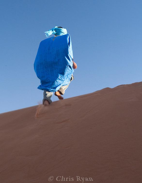 Berber in blue running up sand dunes, Merzouga, Sahara Desert, Morocco