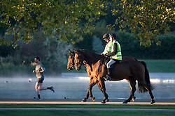 © Licensed to London News Pictures. 24/09/2018. London, UK. A man jogs last two horse riders on a cold Autumn morning in Hyde Park, central London. Photo credit: Ben Cawthra/LNP