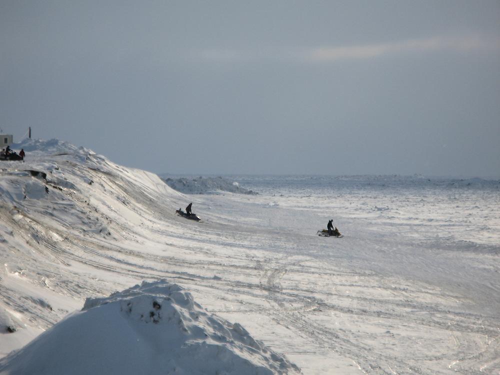 Barrow, Alaska, USA. Snow machines at the beach during Spring.